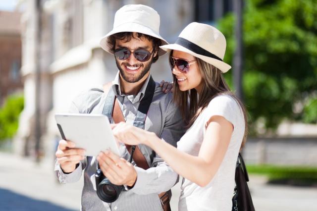 touristes etrangers regardant une tablette