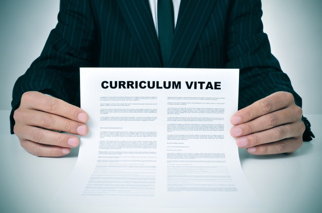 a man wearing a suit showing his curriculum vitae